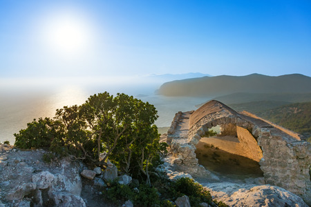 View of Aegean Sea, sunset and ruin of stone arch of Monolithos castle (Rhodes, Greece)