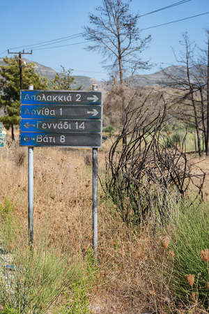 Road sign to villages: Apolakkia, Arnitha, Genandi, Vati, burnt after bushfire (Rhodes, Greece)