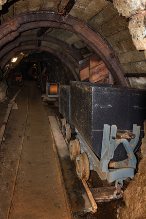Old metal mine train with rusty wheels in mine tunnel with wooden timbering
