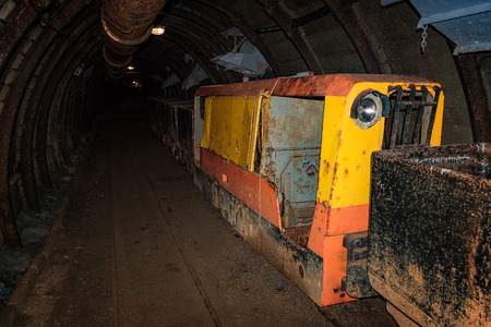 Old and rusty metal mine train with wagons in mine tunnel with wooden timbering