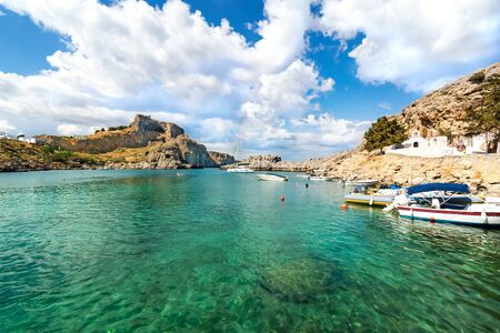 Lindos – view of St. Paul bay, motor boats anchored near orthodox church and acropolis of Lindos in background (Rhodes, Greece) Reklamní fotografie