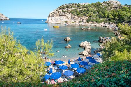 Small beach with tourists, umbrellas and sun chairs in Anthony Quinn bay (Rhodes, Greece) Reklamní fotografie