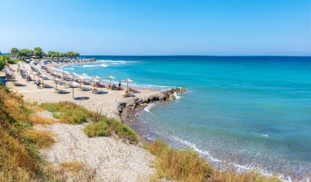 Beach with people, umbrellas and sunbeds near ancient city of Kamiros (Rhodes, Greece)