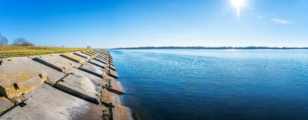 Gabcikovo Dam with bank made of concrete blocks on sunny day Stock fotó