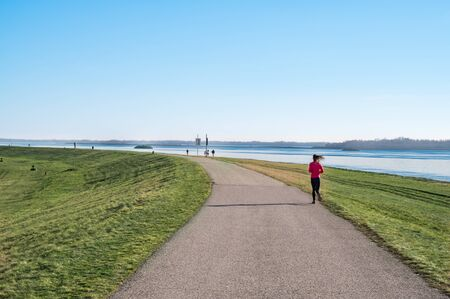 Young girl runs on asphalt walk along bank of Gabcikovo Dam on sunny day