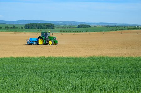 Tractor sowing crops at grain field, blue sky