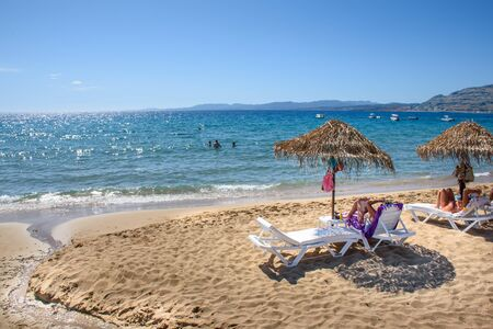 Pefkos beach with holiday-makers, sun beds and umbrellas in village of Pefkos (Rhodes, Greece)
