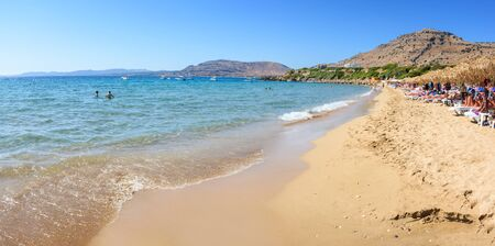 Pefkos beach with holiday-makers, sun beds and umbrellas in village of Pefkos - PANORAMA (Rhodes, Greece)