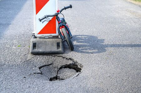 Balance bike (push bike) lean against detour alert traffic sign near pothole on asphalt street with  Stock fotó