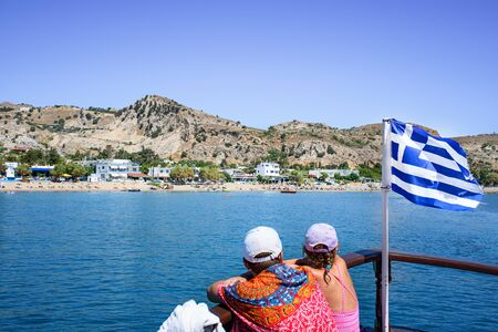 Young couple look at Stegna beach from prow of tourist boat. Next to them Greek flag. (RHODES, GREECE) Stock fotó