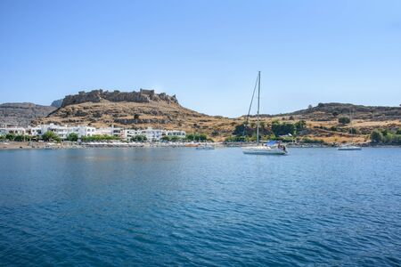 View of sailing boat near Haraki beach with ruin of castle on hilltop (Rhodes, Greece)