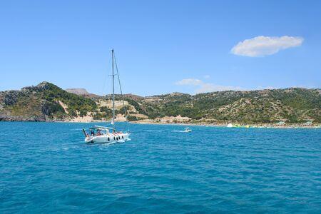 White sailboat heading to Tsambika beach (RHODES, GREECE)