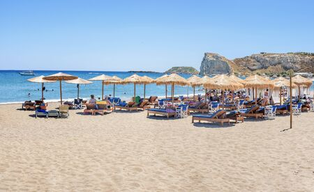 Holiday-makers, sun beds and umbrellas on Stegna beach (RHODES, GREECE)