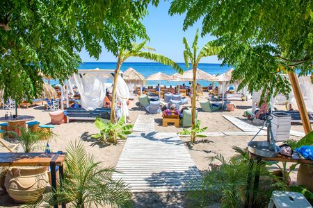 Umbrellas, sun beds and holiday-makers on Stegna beach (RHODES, GREECE)