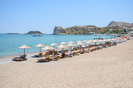 Stegna beach with sunbeds and umbrellas, holidaymakers sun bathing (RHODES, GREECE)  Stock fotó