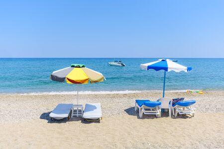 Empty sunbeds with umbrellas on Stegna beach (RHODES, GREECE)