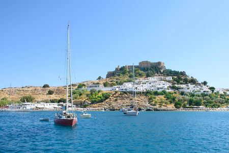 Sailing boats anchored in bay right under Village of Lindos with Acropolis on hill (Rhodes, Greece)