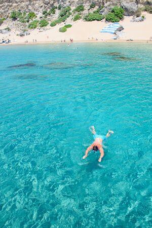 Man snorkels from Tsambika beach (RHODES, GREECE)