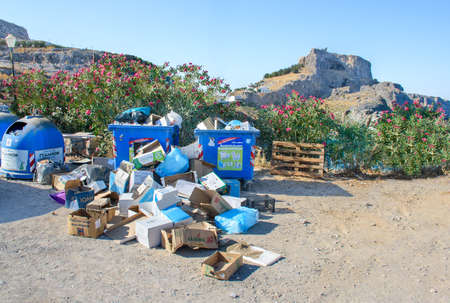 LINDOS (ISLAND OF RHODES), GREECE – AUGUST 8 2019: Pile of rubbish down on ground near plastic litter bin on parking lot. Acropolis of Lindos in background