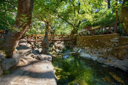 Wooden bridge over small Loutanis river in Seven spring (Epta Piges) in forest near Kolymbia (Rhodes, Greece)