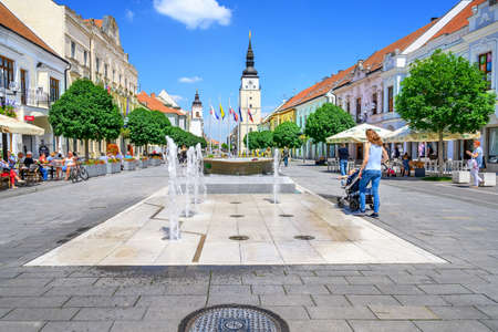TRNAVA, SLOVAKIA – JUNE 25 2020: water fountain on pedestrian zone of city centre of Trnava with town tower in background.