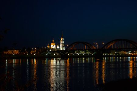 Nocturnal image of the passage of a river through the city where there is a bridge, houses, streetlights and at the end the belfry of the city cathedral.