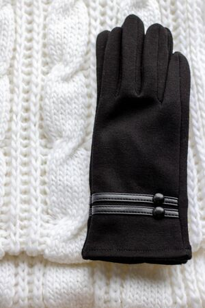 Clothes for a cold season: woolen scarf and gloves. Scarf of white color, glove black. The object is isolated on a white background,
