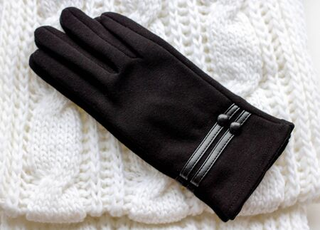 Clothes for a cold season: woolen scarf and gloves. Scarf of white color, glove black. The object is isolated on a white background
