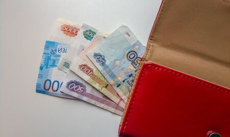 Banknotes of two thousand Russian rubles in brown leather wallet on white background.