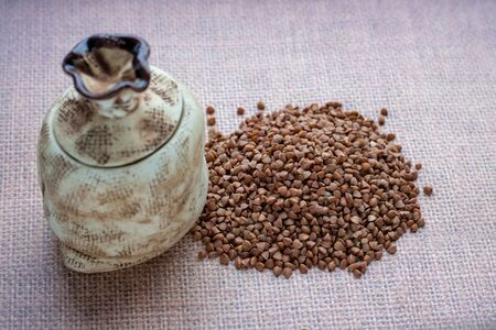 Biologically grown organic buckwheat in a burlap bag with a wooden scoop on a brown background.food