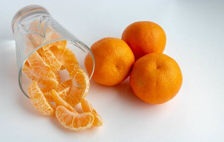 Citrus juice in a clear glass on a light white background. Mandarin, orange close-up. Fruits. Fruits with a high content of vitamin C.food