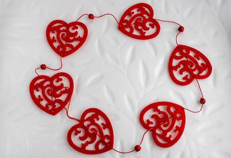 Guirnalda de San Valentín de corazones rojos aislado sobre fondo blanco romántico. Foto de archivo