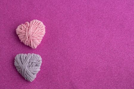 Pink and lilac knitting yarn heart shaped. Valentines day minimal concept. Greeting card with heart on a pink background. Top view. Flat lay. Copy space.