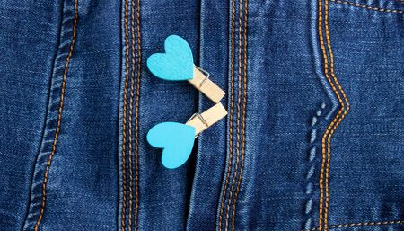 Small wooden heart clothespins fastened to a denim pocket. Small clothespins with blue hearts on the pocket of blue jeans. bacground