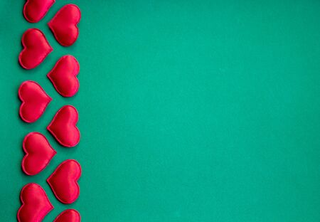 red hearts on a green background. Valentines day card with red hearts.