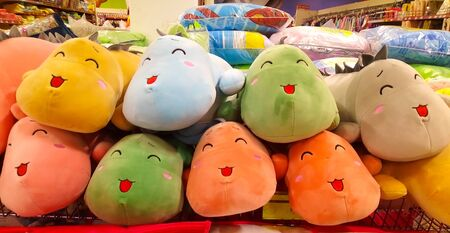 Toy store. Plush toys on shelves in the store for sale with prices. Soft plush toys for children sitting in row.
