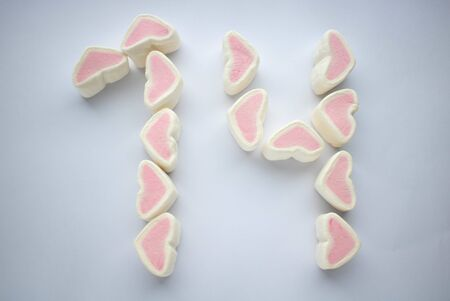 Marshmallow hearts aligned to be number fourteen for valentine's day. on white background.