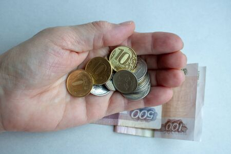The hand of an elderly woman with coins, Rubles from pensioner. Reklamní fotografie