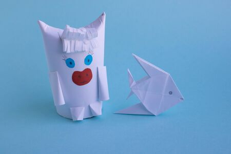 A white fish and a funny white bull made of paper and toilet roll on a blue background.New year's fantasy.