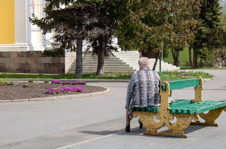 An elderly, tired woman is sitting on an old bench with her back to the sun.