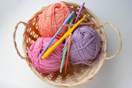 Balls of colored yarn in a basket on white background.
