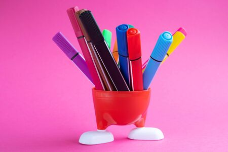 Red stand with white legs and colored markers isolated on a pink background