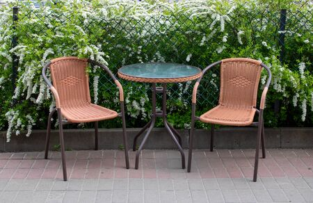 Summer street cafe. The glass table and brown chairs are outdoors. A small cozy restaurant with retro furniture and bushes with white flowers