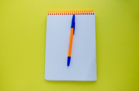 Notepad with an orange spiral and an orange pen, on a yellow background. top view copy space.