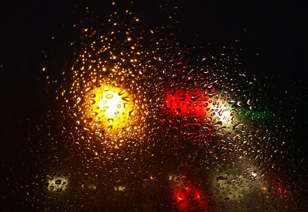 Rain drops on window with road light bokeh,water drop on the glass, night storm raining car driving concept. night car
