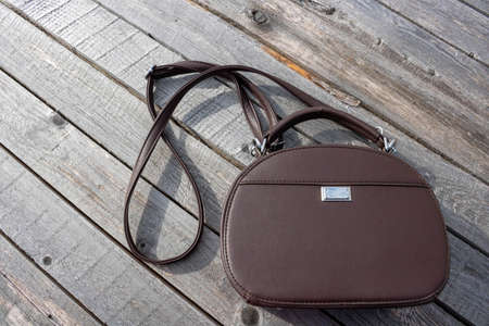 A woman's brown purse is lying on the old gray boards . Space for your text