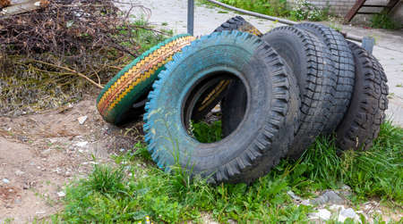 Old dirty tires are lying in the trash. Concept of environment and waste recycling.