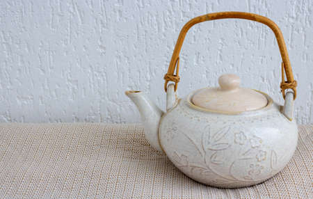 An old light clay teapot with cracks and scratches on a white background