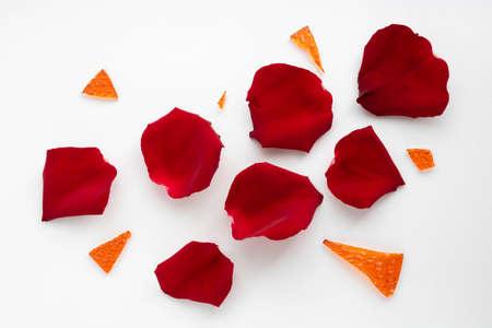 Red rose petals and orange glass shards.