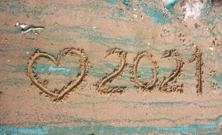 The concept of a New year. Heart and numbers 2021 in the sand. Summer beach holidays. The message is handwritten. Stock fotó